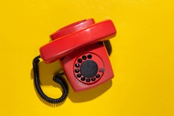 Retro red old fashioned rotary phone on yellow bright background. Top view