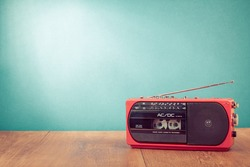 Retro red radio cassette player on table in front mint green background