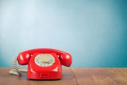 Retro red telephone on wood table near aquamarine wall background