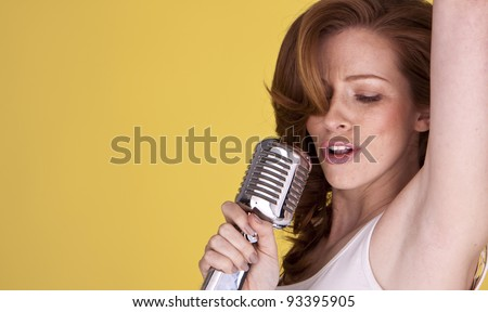 Retro redhead female singer with microphone singing her heart out. Redhead female singer.