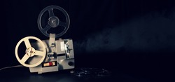 retro reel 8mm movie film projector working in dark room. copy space banner