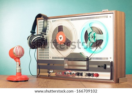 Retro reel to reel tape recorder microphone headphones in front mint green background