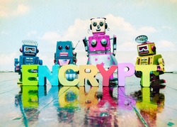 retro robot toys on a old wooden floor with the word ENCRYPT with toy wooden letters