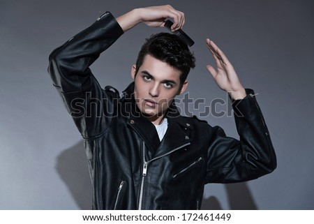 Retro rock and roll 50s fashion man. Combing his hair. Wearing black leather jacket. Studio shot against grey. ストックフォト ©