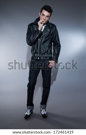 Retro rock and roll 50s fashion man with dark grease hair. Smoking cigarette. Wearing black leather jacket. Studio shot against grey.