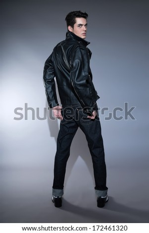 Retro rock and roll 50s fashion man with dark grease hair. Wearing black leather jacket and jeans. Studio shot against grey.