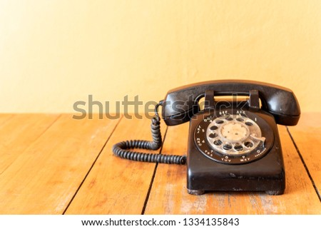Retro rotary old black telephone placed on a wooden table. #1334135843