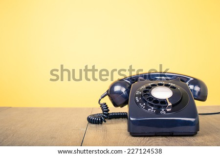 Retro rotary telephone on wood table front yellow wall #227124538