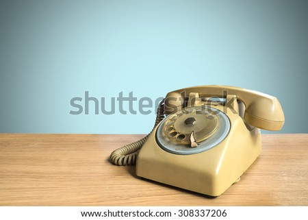 Retro rotary telephone on wooden table with pastel background #308337206