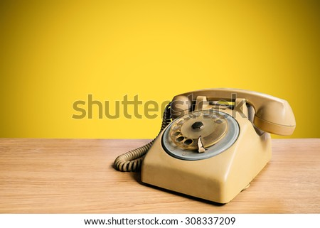 Retro rotary telephone on wooden table with pastel background #308337209