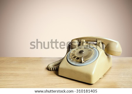 Retro rotary telephone on wooden table with pastel background #310181405