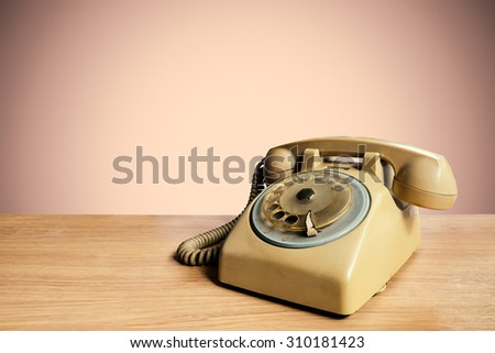Retro rotary telephone on wooden table with pastel background #310181423