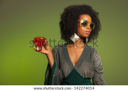 Retro 70s afro fashion woman with green dress and orange cocktail glass. Green background.