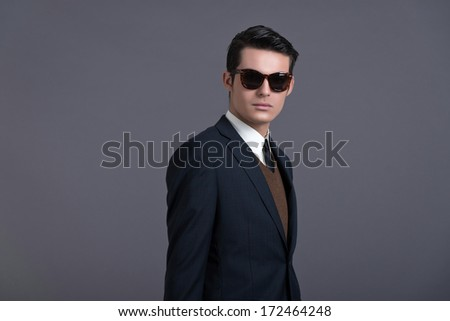 Retro 50s business fashion man with dark grease hair. Wearing dark blue suit and sunglasses. Studio shot against grey. ストックフォト ©
