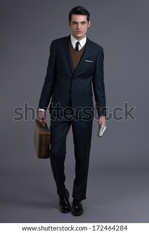 Retro 50s business fashion man with dark grease hair. Wearing dark blue suit and tie. Holding vintage suitcase. Studio shot against grey.
