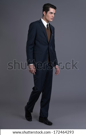 Retro 50s business fashion man with dark grease hair. Wearing dark blue suit and tie. Studio shot against grey.