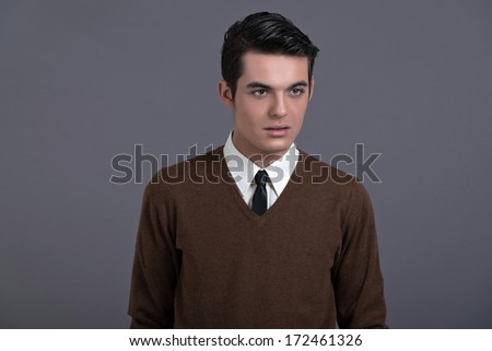 Retro 1950s fashion man with dark grease hair. Wearing brown sweater with black tie. Studio shot against grey. ストックフォト ©