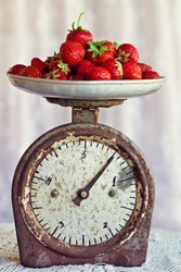 retro scales with a handful of fresh ripe strawberries