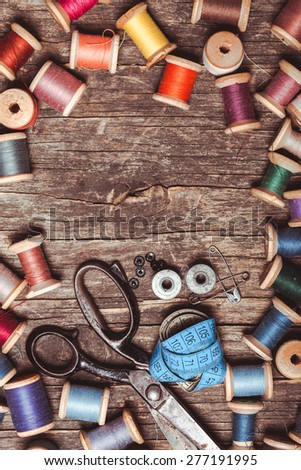 Retro scissors, textile and sewing threads on the wooden table with copy space