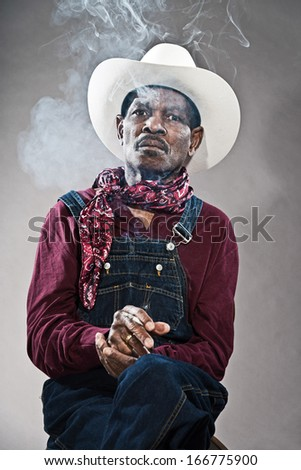 Retro senior afro american blues man in times of slavery. Wearing denim bib and brace overall with white hat. Smoking a cigarette.