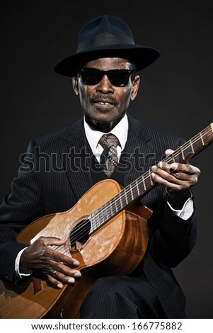 Retro senior afro american blues man. Wearing striped suit with blue hat and black sunglasses. Playing acoustic guitar.
