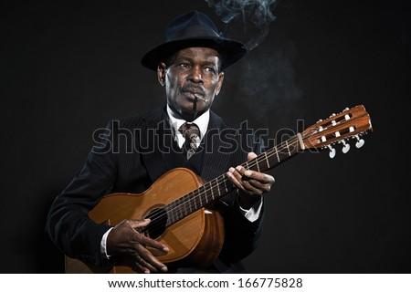 Retro senior afro american blues man. Wearing striped suit with blue hat. Playing acoustic guitar. Smoking cigar. - stock photo