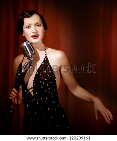 Retro singer sing holding vintage microphone - stock photo