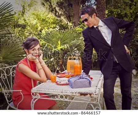 retro sixties style fashion couple having breakfast outdoor