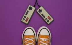 Retro sneakers (gumshoes) with retro joystick on purple background. Top view. 80s. Flat lay