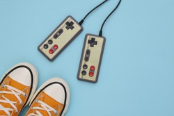 Retro sneakers (gumshoes) with retro joysticks on blue background. Top view. 80s. Flat lay