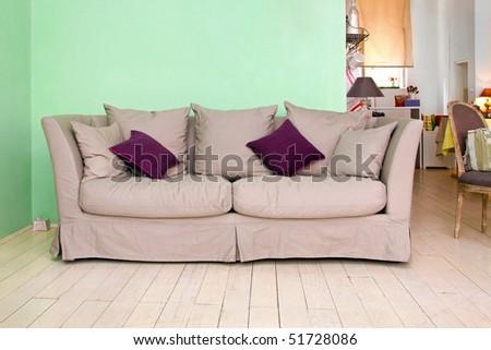 Retro sofa in vintage interior with purple cushions