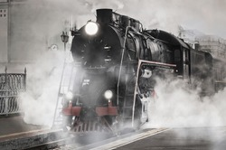 Retro steam train departs from the railway station.
