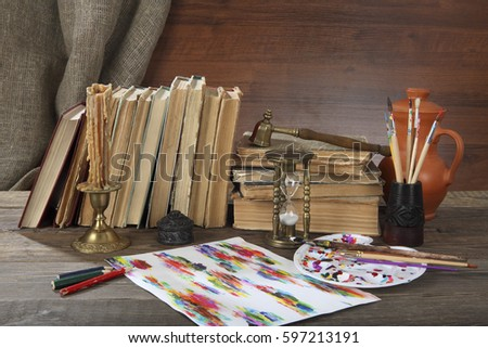 Retro still life. On the desktop is: a jug, a candle in an ancient bronze candlestick, an hourglass, tassels with a malbert, pencils and old books #597213191