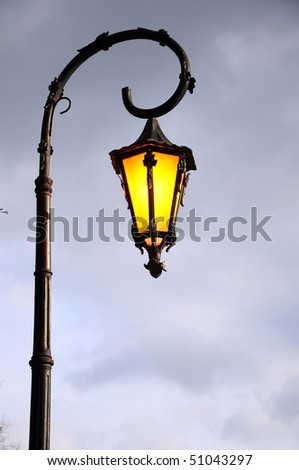Retro street lamp shining at night against cloudy sky