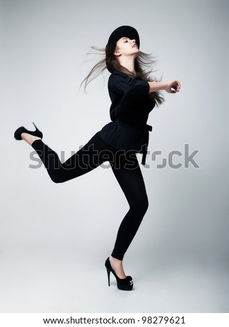 Retro style. Fashion Model Pin-up Girl in Black Clothing Running in studio