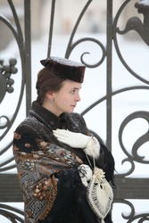 Retro style fashion. Russian girl in vintage folk Pavlovo Posad shawl, scarf and ancient brown hat. Architecture of old center in Moscow city, Russia. Gate of Morozova House on Spiridonovka Street, 17