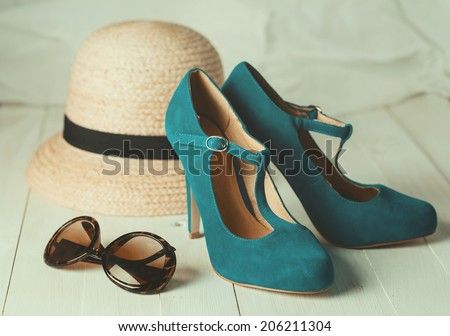 Retro style image of female fashion: straw hat, sun glasses and turquoise shoes over white wooden background. Selective focus, shallow DoF, vintage filters