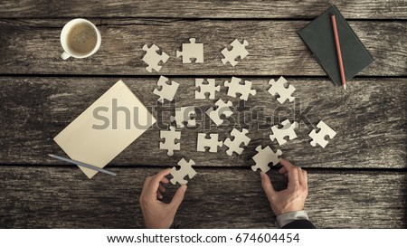 Retro style image of male hands in business suit trying to find a solution to a problem by arranging and matching puzzle pieces on a textured rustic wooden desk, top view. #674604454