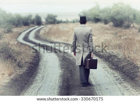 Retro style man on the country road, view from back