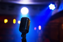 Retro style microphone on stage in the spotlight performance of the musical group. Microphone for rock, rock'n'roll and rockabilly music. Microphone in blue light og stage. Music is in the air