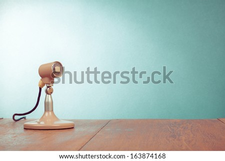 Retro style microphone on table front  mint green wall background