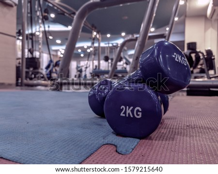 Retro style of a pair of small blue dumbbells of 2 kilograms placed on rubber gym floor with different gym interior equipment around for weight loss and strength training
