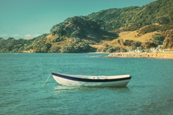 Retro-style photo of a wooden row boat moored in calm waters of the bay on a summer day. Green mountain slopes at the distance. Toned image