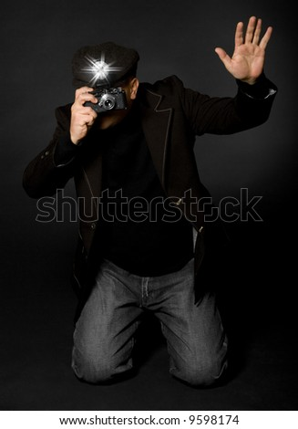 Retro style photographer with vintage camera and flash holding up his hand taking a picture