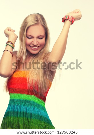 Retro style.Portrait of happy young adult woman dancing with her hands behind head.