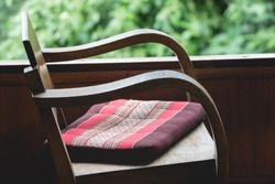Retro style wooden chair with square cushion in front of a window with green trees background.
