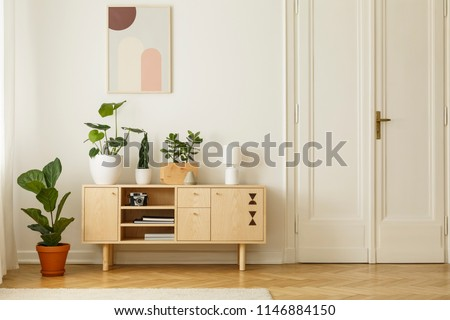 Retro style, wooden sideboard with green plants and a poster on a white wall in a simple apartment interior with herringbone hardwood floor. Real photo.