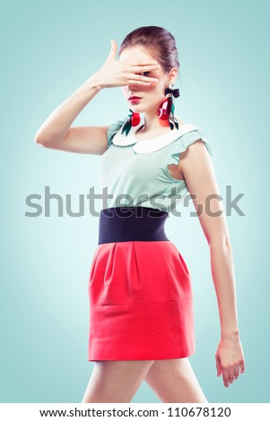 Retro style young woman closed her face with one hand but looking at the camera between her fingers. She's wearing big fancy earrings, blue background