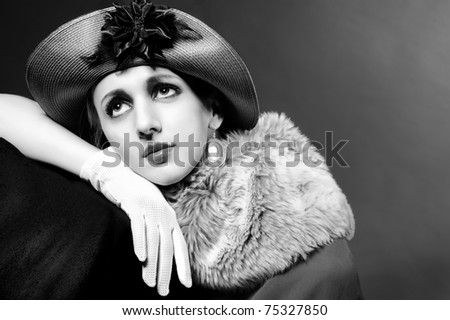 Retro styled fashion portrait of a young woman in hat. Clothing and make-up in vintage style