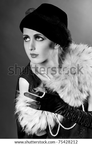 Retro styled fashion portrait of a young woman with pearls. Clothing and make-up in vintage style